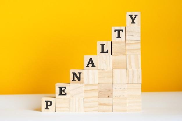 Le mot pénalité est écrit sur des cubes en bois. blocs sur un fond jaune vif. concept de hiérarchie d'entreprise et marketing à plusieurs niveaux. mise au point sélective