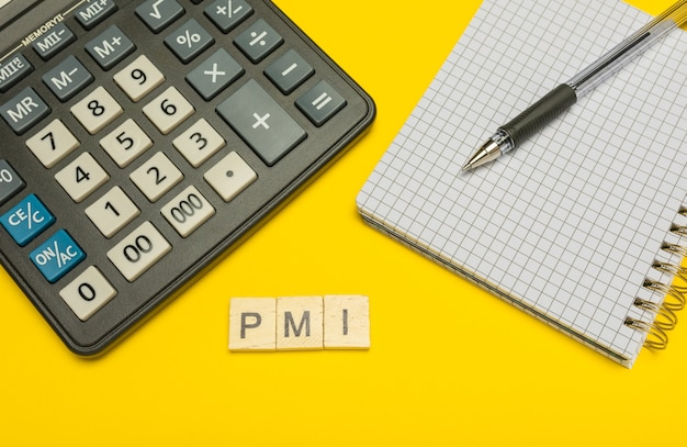 Mot pmi fait avec des lettres en bois sur une calculatrice jaune et moderne avec un stylo et un cahier.