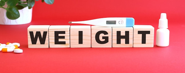 Le mot poids est composé de cubes en bois sur fond rouge avec des médicaments.