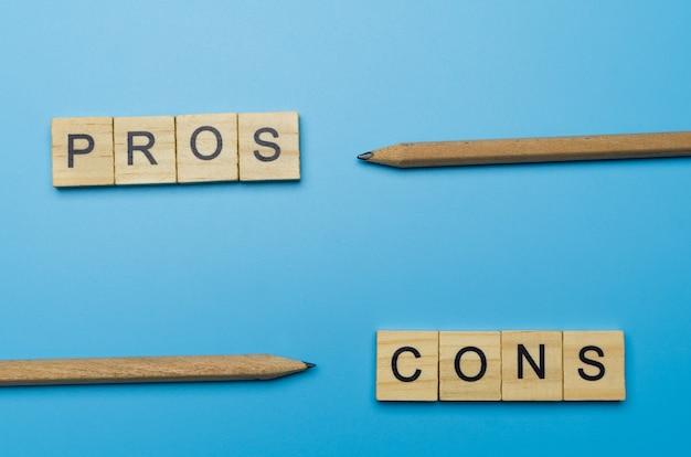 Mot «pour et contre» dans le bloc de bois sur une surface bleue pointée au crayon