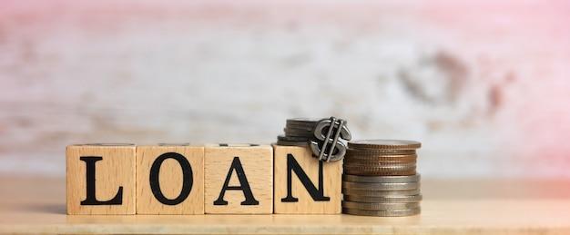 Mot de prêt écrit sur bloc de bois et pièces de monnaie mis sur planche de bois