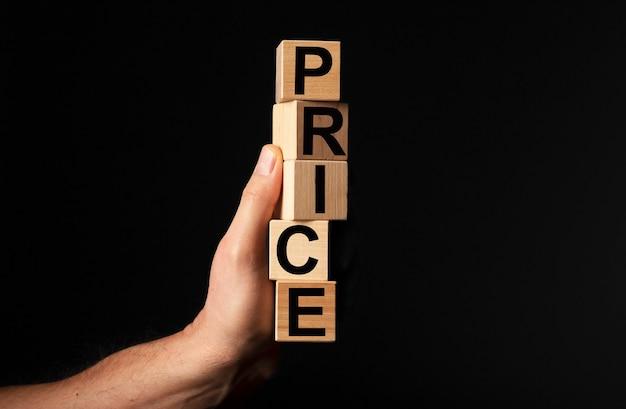 Mot de prix dans les dés en bois dans la main masculine sur fond noir