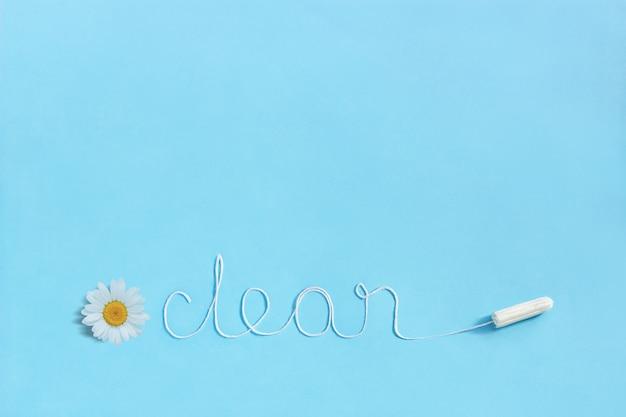 Mot propre de tampon hygiénique femelle de fil blanc et camomille sur bleu