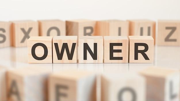 Mot de propriétaire à partir de blocs de bois avec des lettres, propriétaire ou concept d'entreprise, lettres aléatoires autour, fond blanc