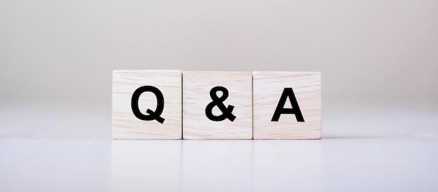 Mot de q&a avec bloc de cube en bois. faq (questions fréquentes)