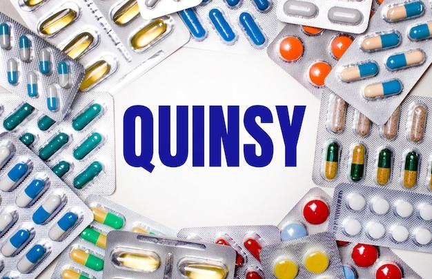Le mot quinsy est écrit sur un fond clair entouré d'emballages multicolores avec des pilules. notion médicale