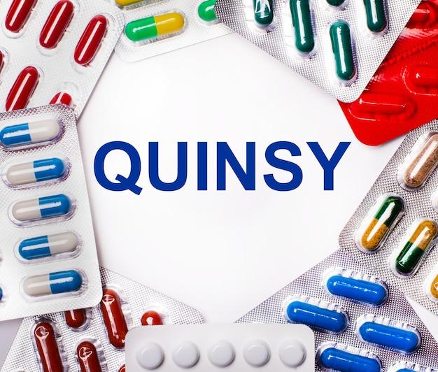 Le mot quinsy est écrit sur une surface claire entourée d'emballages multicolores avec des pilules