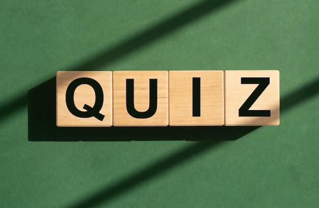 Mot de quiz sur des cubes en bois sur le concept de jeu de quizz de fond ensoleillé vert
