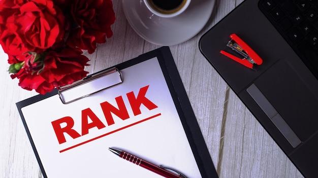 Le mot rank est écrit en rouge sur un bloc-notes blanc près d'un ordinateur portable, d'un café, de roses rouges et d'un stylo.