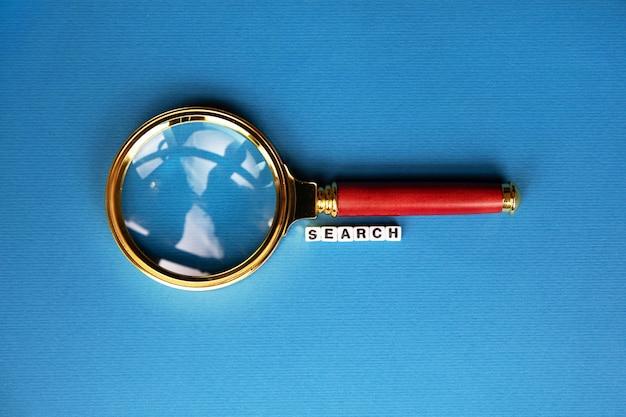 Mot de recherche à travers la loupe sur fond bleu à la mode