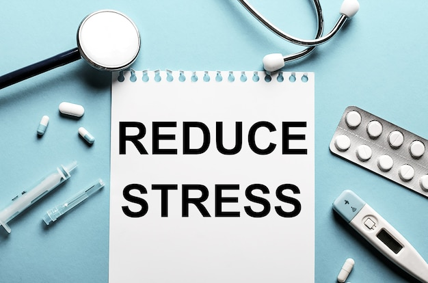 Le mot réduire le stress écrit sur un bloc-notes blanc sur un mur bleu près d'un stéthoscope, d'une seringue, d'un thermomètre électronique et de pilules. concept médical