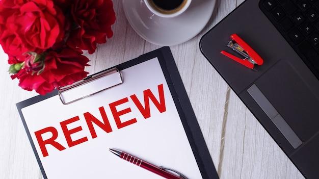 Le mot renew est écrit en rouge sur un bloc-notes blanc près d'un ordinateur portable, d'un café, de roses rouges et d'un stylo.