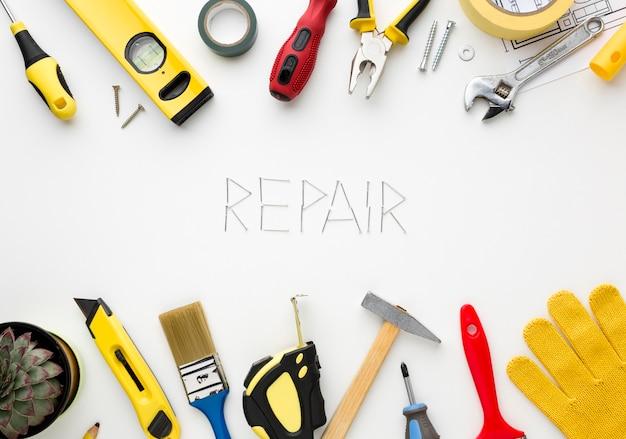 Mot de réparation écrit avec des clous entourés d'un kit de réparation