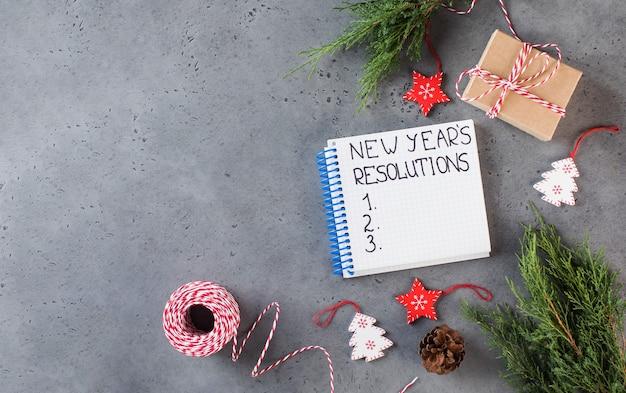 Le mot résolution du nouvel an écrit dans un cahier blanc sur un espace de copie de fond gris du nouvel an