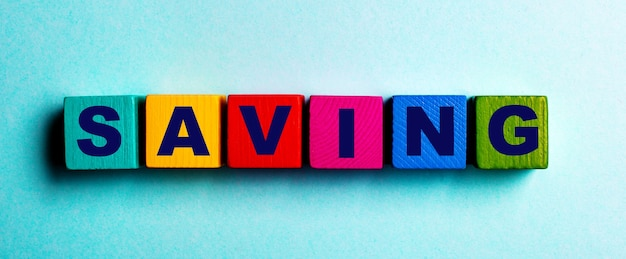 Le mot saving est écrit sur des cubes en bois lumineux multicolores sur fond bleu clair