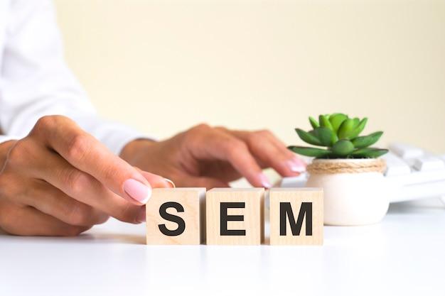 Le mot sem, épelé sur des cubes en bois avec des lettres sur fond blanc. indice de force relative