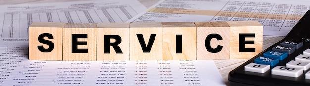 Le mot service est écrit sur des cubes en bois près des graphiques et de la calculatrice.