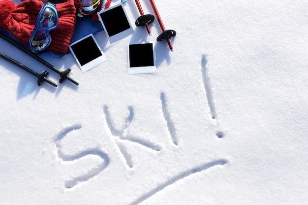 Le mot ski écrit dans la neige avec des bâtons de ski, des lunettes et des chapeaux et des tirages photo vierges