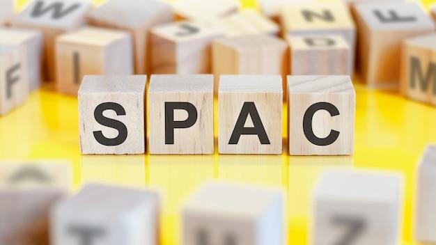 Le mot spac est écrit sur une structure de cubes en bois. blocs sur un fond clair. notion financière. mise au point sélective. spac - abréviation de société d'acquisition ad hoc