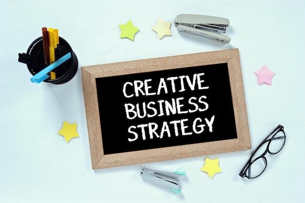 Mot de stratégie d'entreprise créative sur la vue de dessus sur le tableau noir