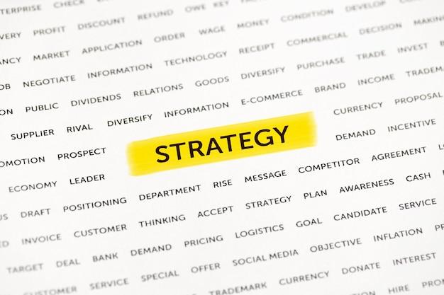 Le mot «stratégie» est mis en évidence avec un marqueur sur papier. concept d'entreprise, stratégie, planification, succès