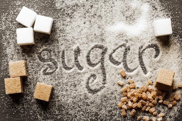 Le mot sucre écrit dans un tas de sucre granulé blanc
