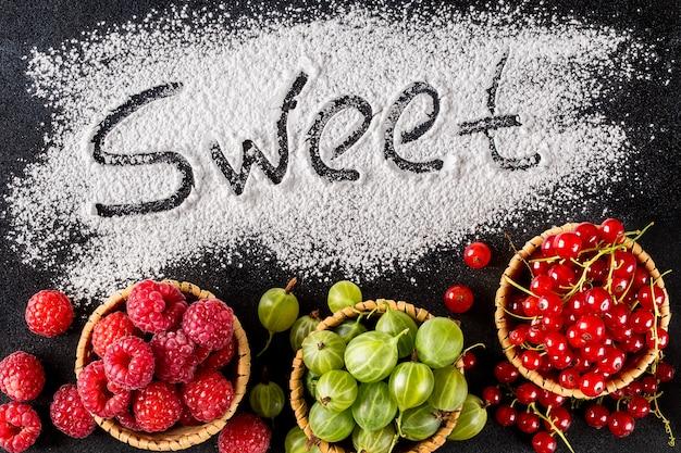 Le mot sweet est sur un fond sombre à côté de baies