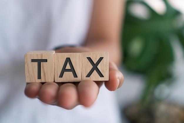 Mot de taxe sur un cube en bois. concept de propriété de prêt financier commercial.