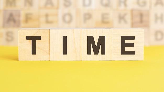 Le mot temps est écrit sur des cubes en bois sur une surface jaune vif. en arrière-plan, des rangées de cubes avec des lettres différentes. concept commercial et financier