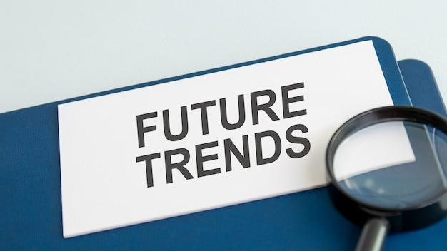 Mot des tendances futures sur une carte en papier blanc et une loupe
