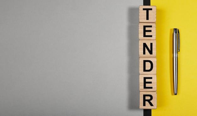 Mot tendre sur des cubes en bois sur fond jaune et gris avec espace de copie pour la bannière d'entreprise de texte avec ...