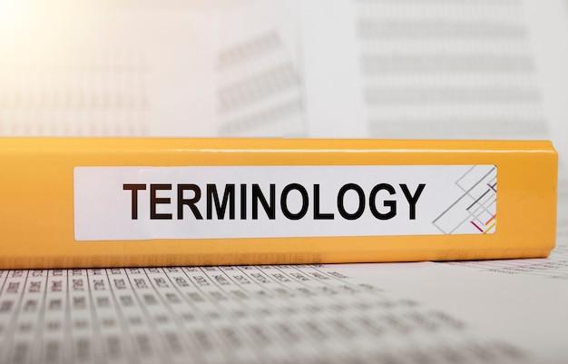 Mot de terminologie sur le dossier de bureau jaune vif sur les documents financiers concept de termes en finance b...