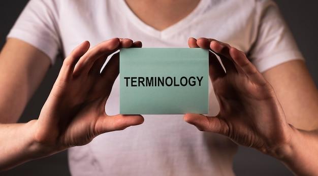 Mot de terminologie sur papier note dans les mains des femmes