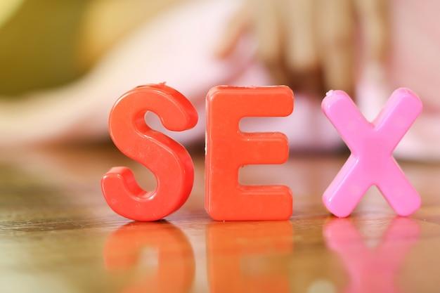 Le mot ou le texte sexe écrit dans l'alphabet avec des lettres colorées avec une main floue