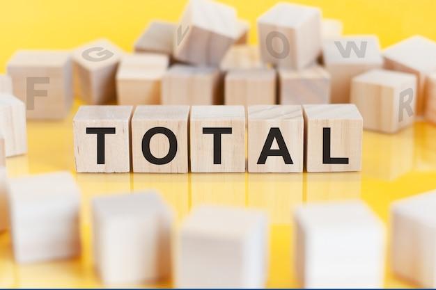 Le mot total est écrit sur une structure de cubes en bois. blocs sur un fond clair. notion financière. mise au point sélective