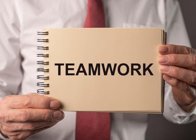 Mot de travail d'équipe entre les mains de l'homme d'affaires. concept de travailler ensemble en communauté.