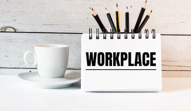 Le mot travail est écrit dans un bloc-notes blanc près d'une tasse de café blanc sur un mur léger
