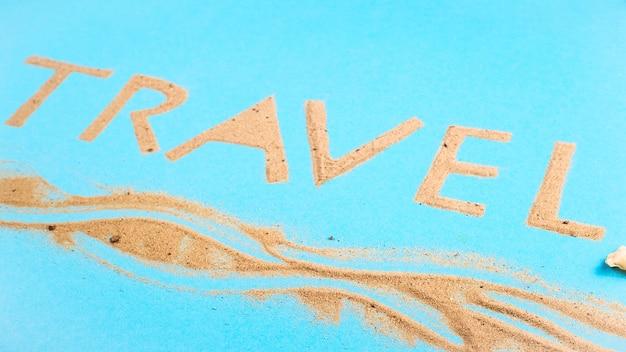 Le mot travel écrit avec du sable de plage - un concept de vacances à la mer.