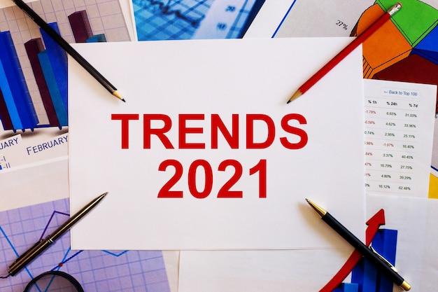 Le mot trends 2021 est écrit sur un fond blanc à proximité de graphiques colorés, de stylos et de crayons. concept d'entreprise