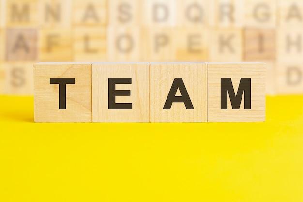 Le mot vendu est écrit sur des cubes en bois sur une surface jaune vif. en arrière-plan, des rangées de cubes avec des lettres différentes. concept commercial et financier