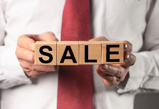 Mot de vente sur des blocs de cube en bois dans les mains d'un homme d'affaires