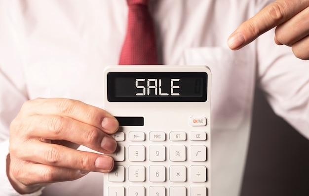 Mot de vente sur la calculatrice dans la main de l'homme d'affaires