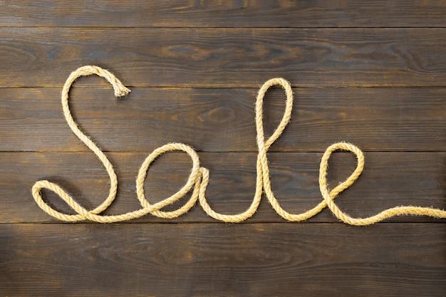 Mot vente est écrit d'une corde de jute brute sous la forme d'une pièce reposant sur une planche de bois texturée brune