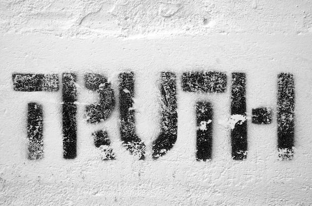 Mot de vérité imprimé au pochoir texturé sur le mur de briques blanches
