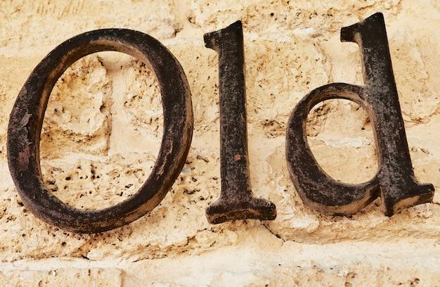 Le mot vieux en lettres métalliques sur fond de pierre.
