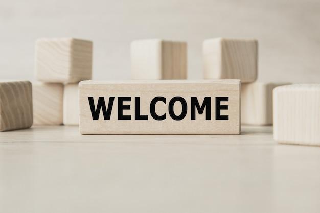 Le mot welcome est écrit sur une structure de cubes en bois.