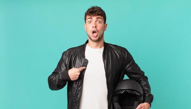 Un motard a l'air choqué et surpris avec la bouche grande ouverte, pointant vers lui-même