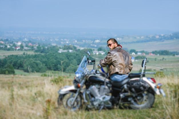 Motard avec barbe assis sur sa moto par une journée ensoleillée