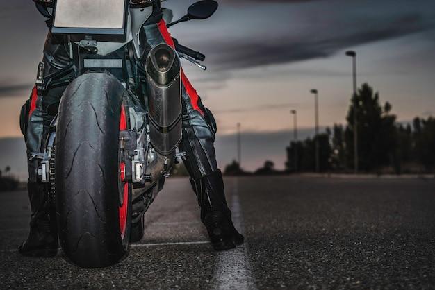 Un motard méconnaissable assis sur une moto de sport noire sur une route asphaltée au crépuscule sous un ciel nuageux. espace de copie.