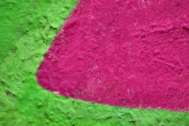 Le motif abstrait sur le mur est peint en fond rose et vert juteux